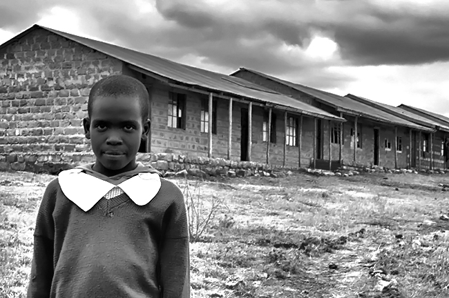 black and white photo of young african girl in front of school in rural Kenya