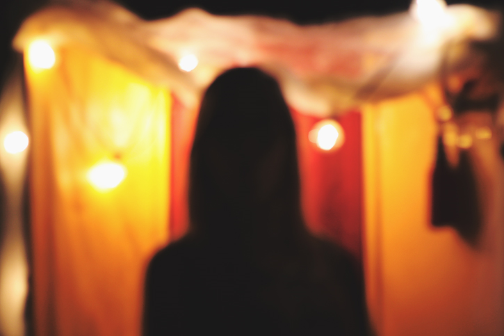 Emilee fromm in eugene oregon at a circus themed party with party lights creating her silhouete